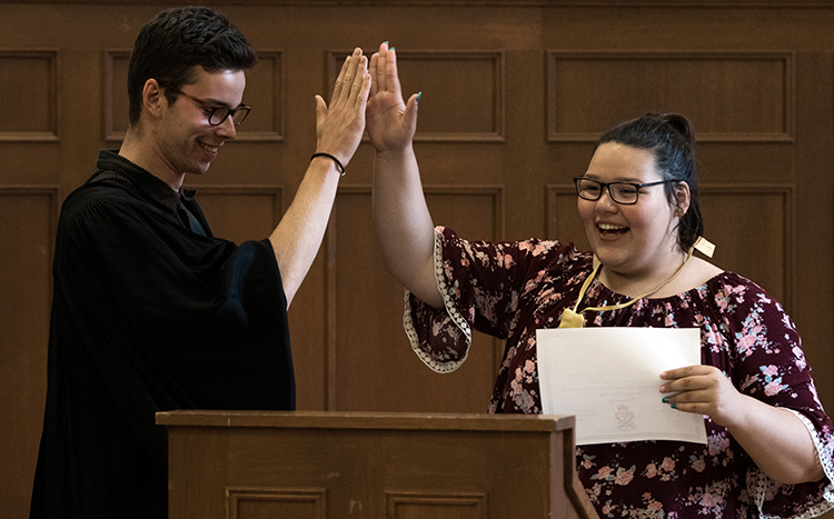 A student and mentor high-five each other.