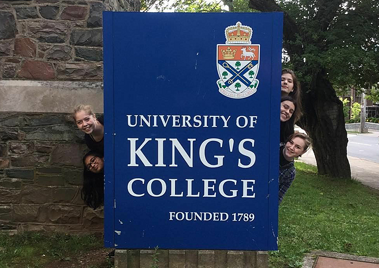 Students peek out from behind the King's sign.